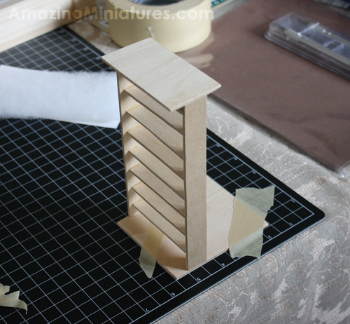 The glue drying on the dollhouse miniature modern bed frame