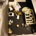 disorganized box of dollhouse miniatures